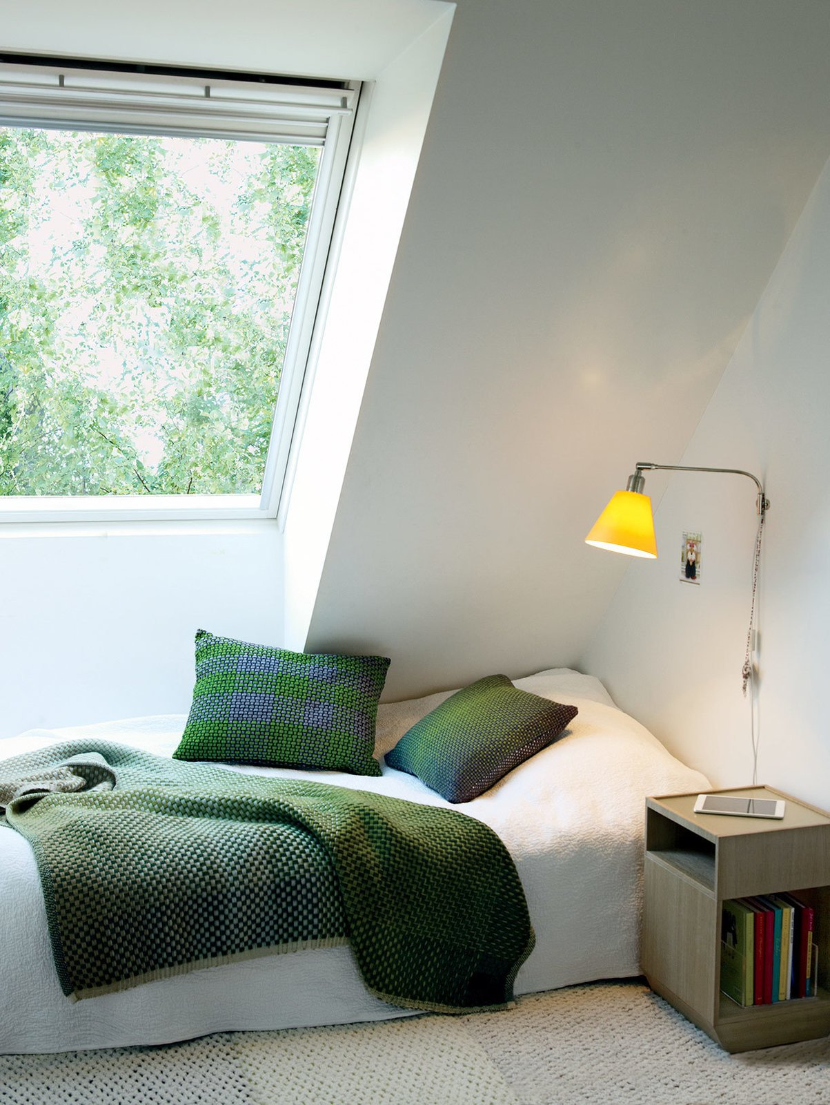 Bedroom and Bed Upstairs, each daughter's bedroom was designed as a sanctuary, with cozy touches like Simon Key Bertman quilts and cushions. The bed and Pile bedside table by Jessica Signell Knutsson sit on top of a Carpet Honeycomb by designer Maria Löw.  Photo 8 of 12 in This Bright Green Prefab in Sweden Looks Just Like a Monopoly House