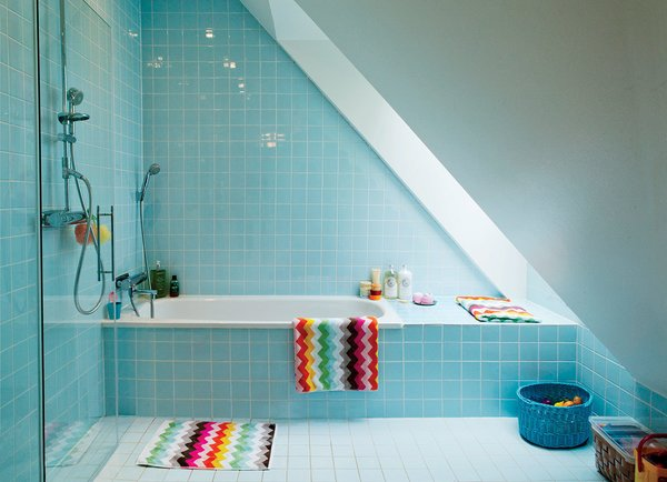 Six-inch-square blue tiles cover the walls and floor of the girls' upstairs bathroom. The towels and rug are also by H&M Home.