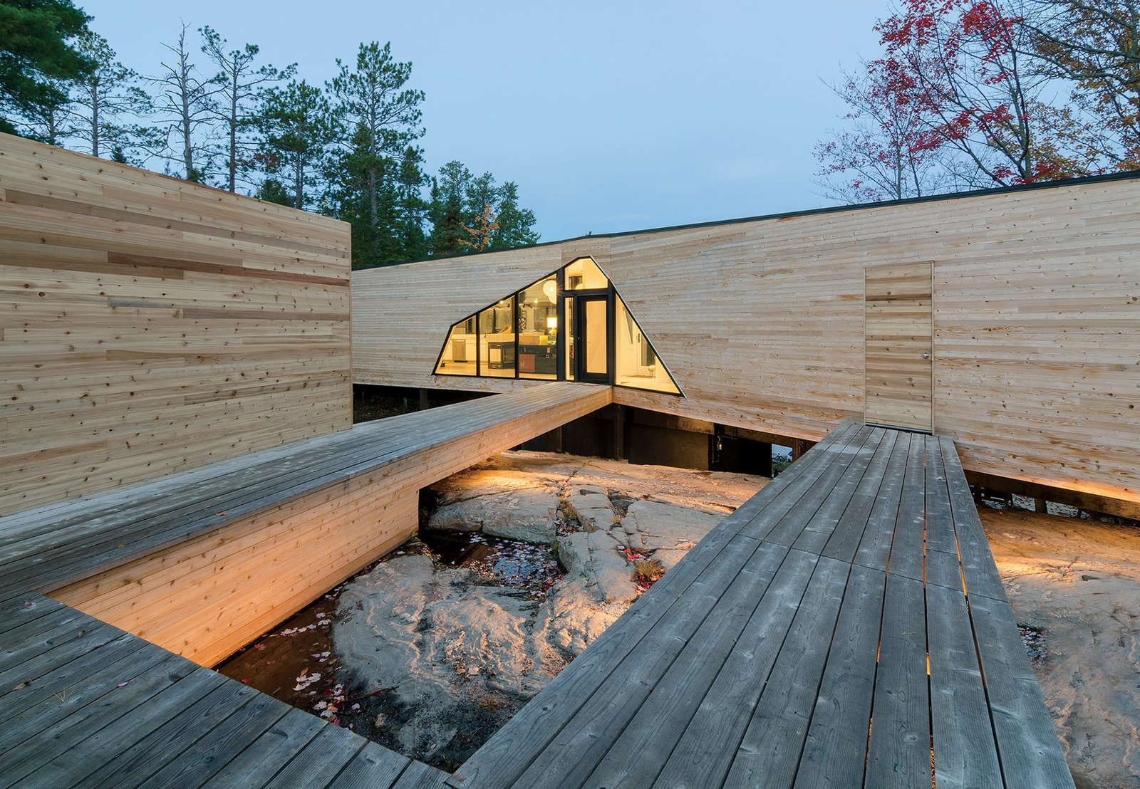 """Outdoor, Wood Patio, Porch, Deck, and Large Patio, Porch, Deck The three-bedroom home is connected to a dock house, garage, and vegetable garden by a network of wood walkways and decks.  Search """"hans bolling wooden duck"""" from Prefab Made This Super Remote House in the Ontario Wilderness Possible"""