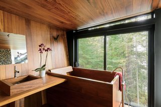 The Japanese-style bathroom, which is clad in teak, features a matching tub and sink by Bath in Wood.