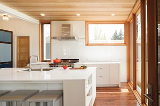 """To maximize light, Dana opted for white surfaces, from the custom cabinetry to the Silestone countertops. """"You can't put a lemon or a Popsicle down on marble, so we got quartz, which is virtually indestructible,"""" she says."""
