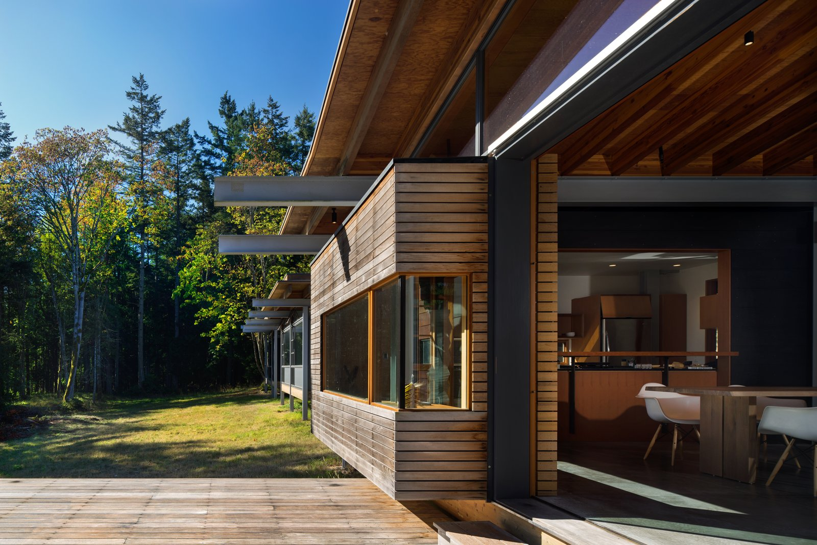 Exterior I-beams extend beyond the house and add a perpendicular gesture to the otherwise elongated home. With virtually no neighbors, the family enjoys a private indoor-outdoor lifestyle. The doors throughout are from Northstar Woodworks.  Photo 8 of 16 in An Off-the-Grid Island Home for a Seattle Music Producer