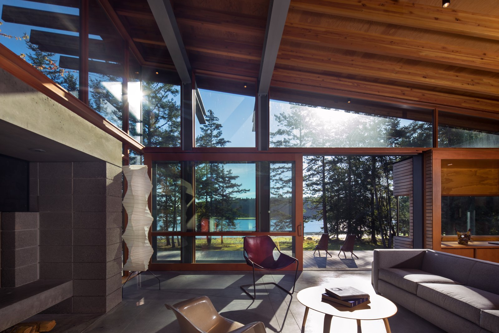 Dominated by a massive concrete fireplace, the living room overlooks the sea. Radiant-heat concrete floors keep the house cozy during winter.  Photo 11 of 16 in An Off-the-Grid Island Home for a Seattle Music Producer