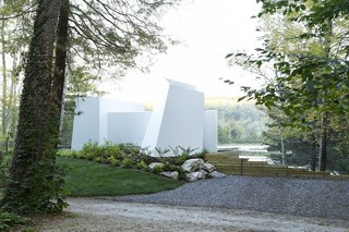 "As the home is approached from the street, the white aluminum facade projects out from the earth in an abstract composition of forms and volumes. There are no doors or windows at the entrance from the road, a calculated decision by the design team to avoid a structure that would read as manmade against the natural landscape. ""We wanted it to feel 'non-architectural' in a way so that the natural view of the lake was not walled off by a privatized notion of someone's home,"" says Miller."