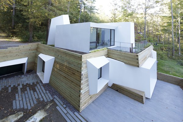 """On the opposite side of the abstract front elevation, the home opens up and presents an entirely different viewing experience. """"Like a flower leaning [towards the] sunlight, the architectural volumes pull and open up towards the views of the lake,"""" says Miller. A stacked timber retaining wall serves both structural and aesthetic functions; in addition to holding back the earth the home has been buried into, it visually defines the its perimeter."""
