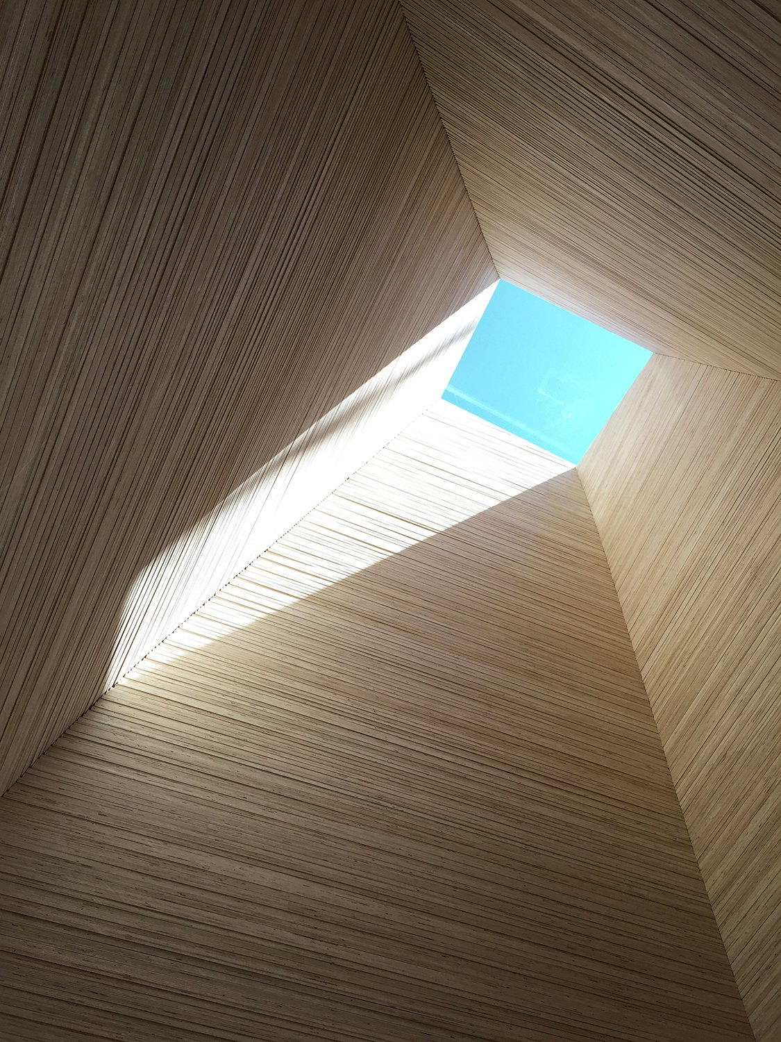"""Windows and Skylight At the entry looking upward towards a Velux skylight, a vertical """"sleeve"""" is made of stacked end grain plywood. The theme of vertical and horizontal architectural elements providing different environmental perspectives carries through to the rest of the home. Horizontal forms look out to the lake, while the vertical columns look up the sky.  Best Windows Photos from An Abstract New England Lake House That Sinks Into the Land"""