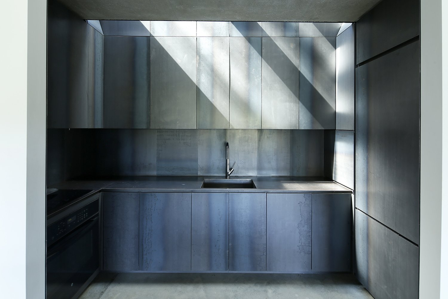 "Kitchen and Metal Cabinet The clients and design team chose to forego an open floor plan in favor of defined, separated spaces. In this scheme, the vertically oriented spaces act as a cinematic ""hard-cut"" to their horizontal counterparts. The custom hot rolled steel kitchen, one of these vertical transition spaces, receives light from above through a Velux skylight. A GE Profile Induction cooktop and oven and Miele refrigerator complete the space.  Photos from An Abstract New England Lake House That Sinks Into the Land"