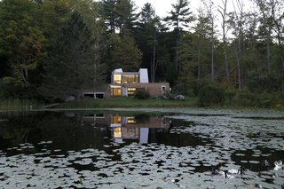 The home's reflection is seen in the lake at dusk. The white aluminum sleeves dramatically break through the timber, creating visual portals to the surrounding scenery.