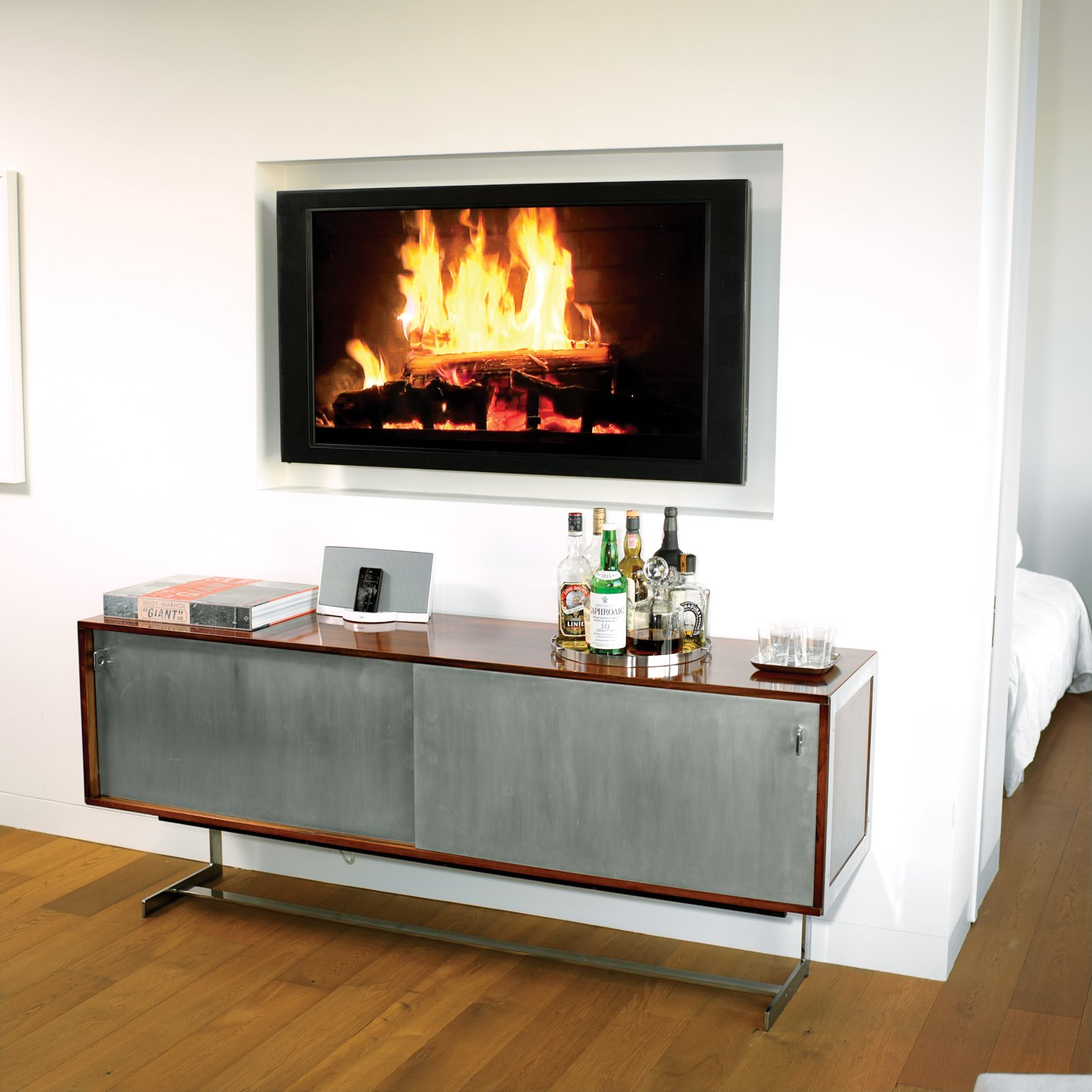 "No room for a built-in bar? Wing it, like architect Cass Calder Smith did in his SoHo apartment, with a modern cabinet, trays to hold bottles and glasses, and a roaring ""fire.""Photo by   Brian Finke.  Search ""fences,-walls--metal"" from High-Rise Living in Manhattan"