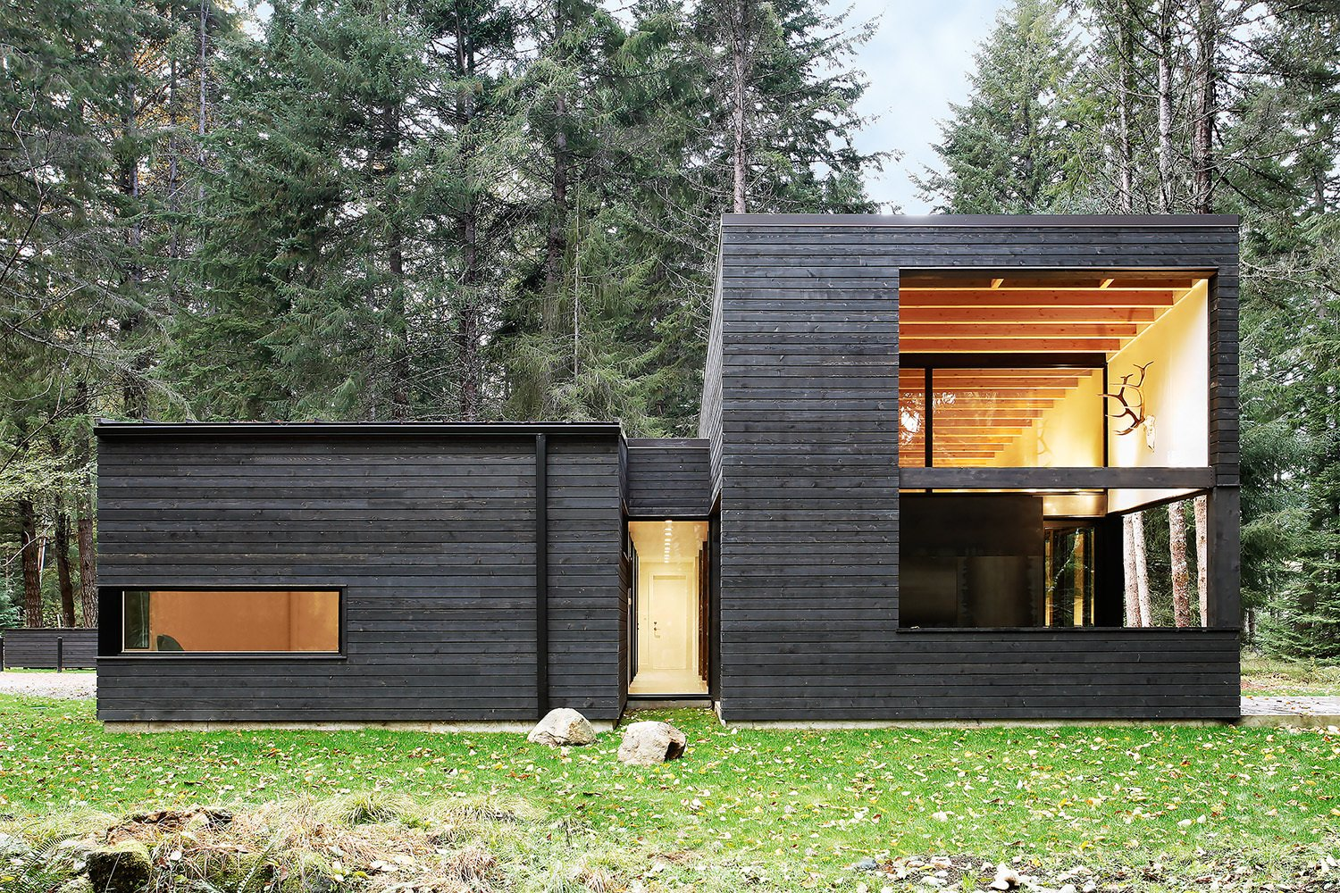"Exterior, Wood Siding Material, House Building Type, and Flat RoofLine ""The cedar siding is simply stained with a black semi-transparent oil stain [from Cabot], which allows the color of the wood to still emerge through,"" architect Robert Hutchison says. ""We love how the black color makes the building recede into the background, and how it in turn allows the trees on the site to emerge as the highlight.""  Future home exterior from Courtyard House on a River"