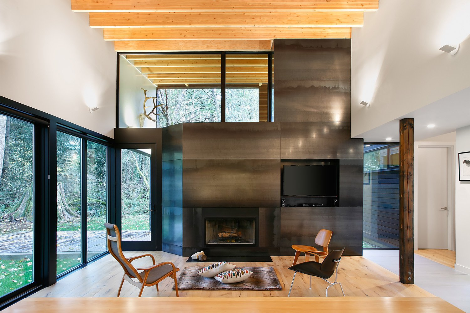 """Living Room, Light Hardwood Floor, Chair, and Standard Layout Fireplace """"From the courtyard, you then enter the house proper, directly into the main living room,"""" Hutchison says. """"From this room, you have a panoramic view looking out through the trees to the river, or back into the courtyard."""" The wood-burning fireplace, from Majestic, is clad in steel panels. Eames Molded Plywood lounge chairs sit side-by-side in the living room.  Courtyard House on a River by Kelly Dawson"""