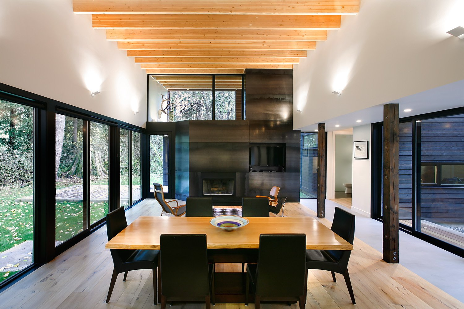 "The home's interior design was intentionally simple: access to light and views were a main priority. ""The roof in this room slopes gradually up to the south, providing a light monitor that brings in southern light filtered through the trees, while providing a framed view of the tops of the trees beyond,"" Hutchison says. Plank flooring by United Tile and Edge wall sconces by Belfer unite the living and dining spaces.  Courtyard House on a River by Kelly Dawson"