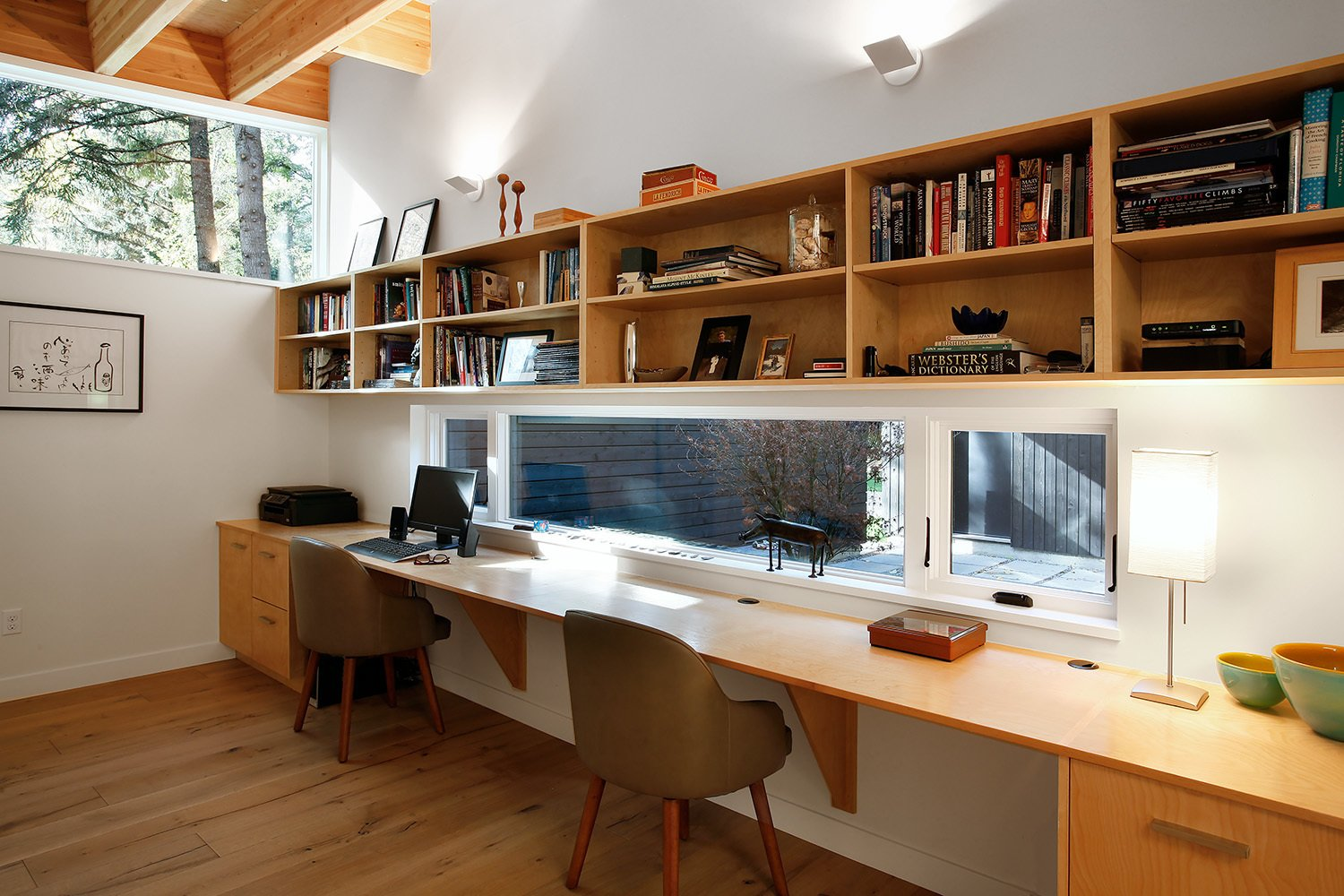 """The roof structure is exposed in every room of the house, which leads the eye to connect all of the rooms together, making the house seem bigger than it really is,"" Hutchison says. Dunn Lumber supplied the laminate shelves for the study.  Shining Examples of Clerestory Windows by Luke Hopping"