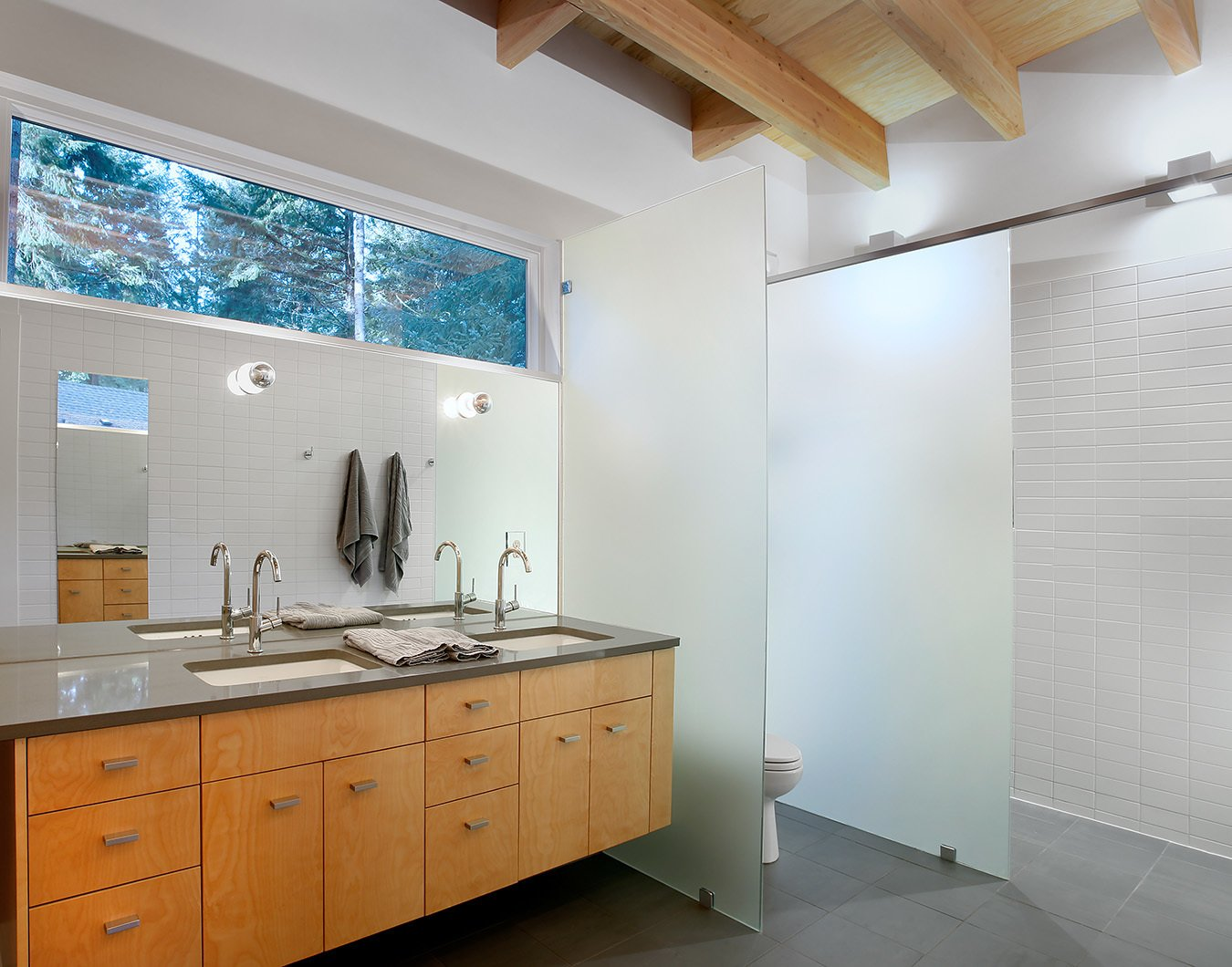 Matching Ladena sinks by Kohler, outfitted with Talis S faucets by Hansgrohe, stand inside polished Stormy Sky countertops by PentalQuartz.  Courtyard House on a River by Kelly Dawson
