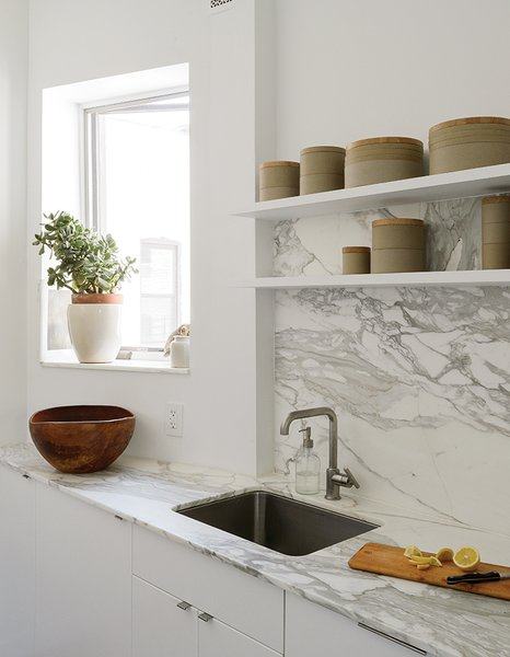 The showstopping material elements are the Borghini honed marble countertop and backsplash by Ann Sacks. Hasami porcelain vessels line the open shelving.