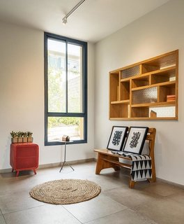 """In Ein Hod, an artists' village founded in northern Israel the 1950s, Ori Dunetz and Eran Naim of EN Design Studio were tasked with creating a a """"pstroal yet modern atmosphere"""" for a librarian and painter with grown children. To connect the pair of boxes that comprise the home, a """"window"""" was created btween the kitchen and office."""