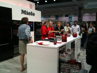 "Miele's ""super booth"" featured live kitchen demos on one half and their new upright vacuum on the other."