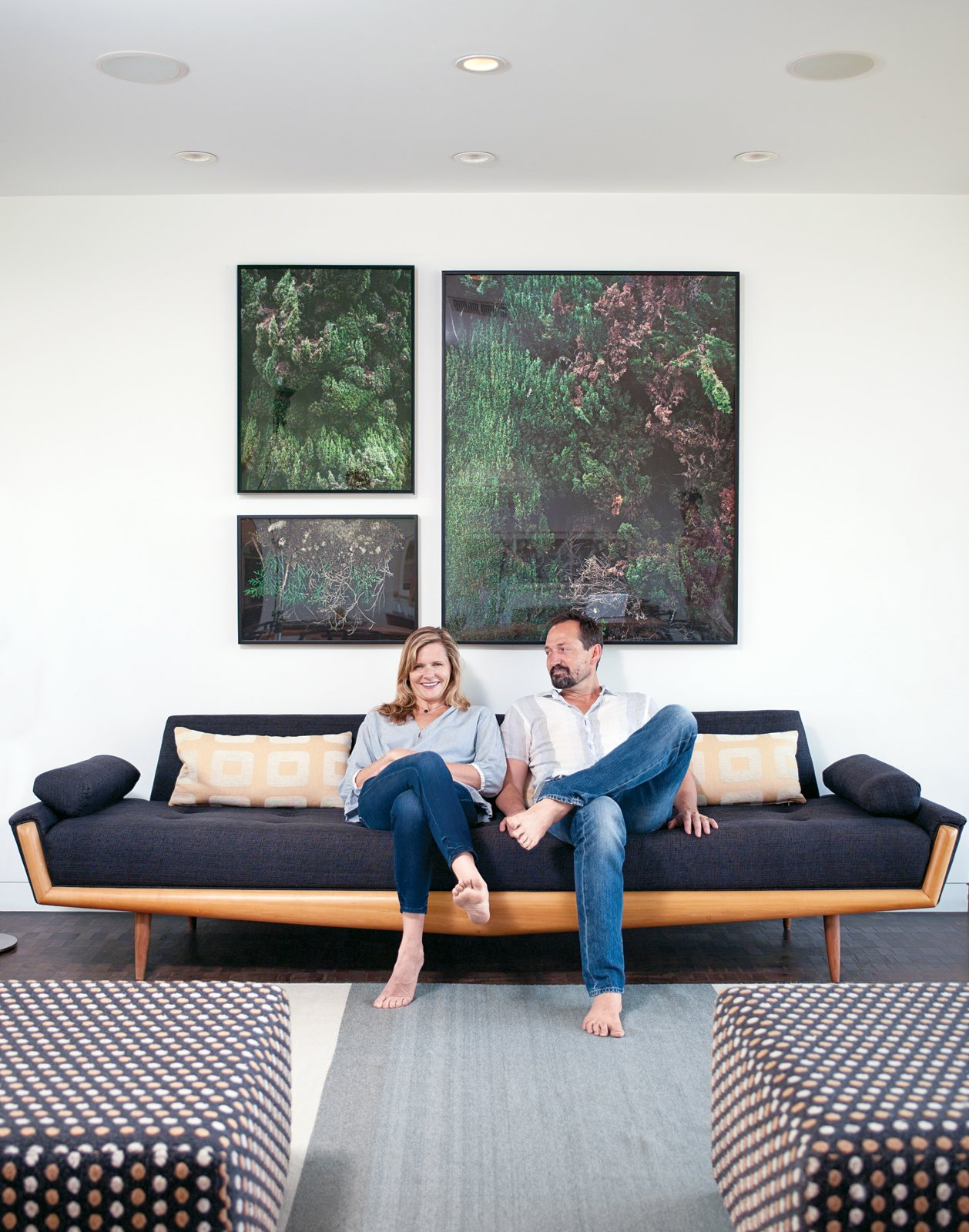 Gabbert and Avery relax on a vintage sofa in their living room beneath large-format photos of juniper bushes by Maegan Hill-Carroll.  Photo 2 of 4 in How to Throw a Great Party in Six Steps from L-Shaped Indoor-Outdoor LA Home