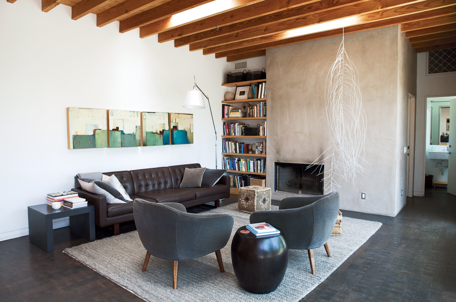 A family room off the kitchen is stocked with pieces from Room & Board, including the Wells sofa and gray Cable rug. The hanging sculpture is by Rebecca Niederlander and the quartet of paintings is by Babak Emanuel.  Photo 6 of 21 in L-Shaped Indoor-Outdoor LA Home