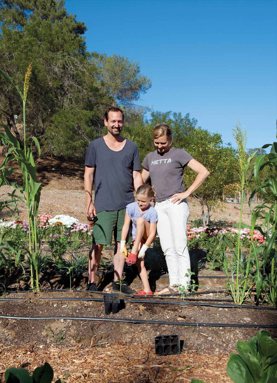 "Gabbert and Avery pose with Ingrid in their ""growing ground,"" planted and tended by local urban farmer Tara Kolla and a fleet of volunteers.  Photo 11 of 21 in L-Shaped Indoor-Outdoor LA Home"