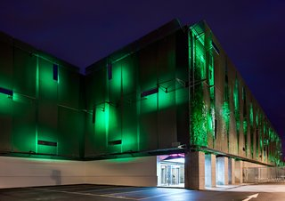 """Singapore Free Port, Exterior, 2010  Grawunder worked closely with Swiss architects Benedicte Montant and Carmelo Stendardo to light this storage facility, designed as the """"ultimate safe"""" for high-value art and collectibles. On the exterior, Grawunder used very low light green LEDs to give a bioluminescent feeling to the wall of plants behind it. In the daytime, the holes where the light comes from reflect the sky. Containing many kilometers of lights, this is Grawunder's largest installation ever """"and probably will be for a long time,"""" she quips."""