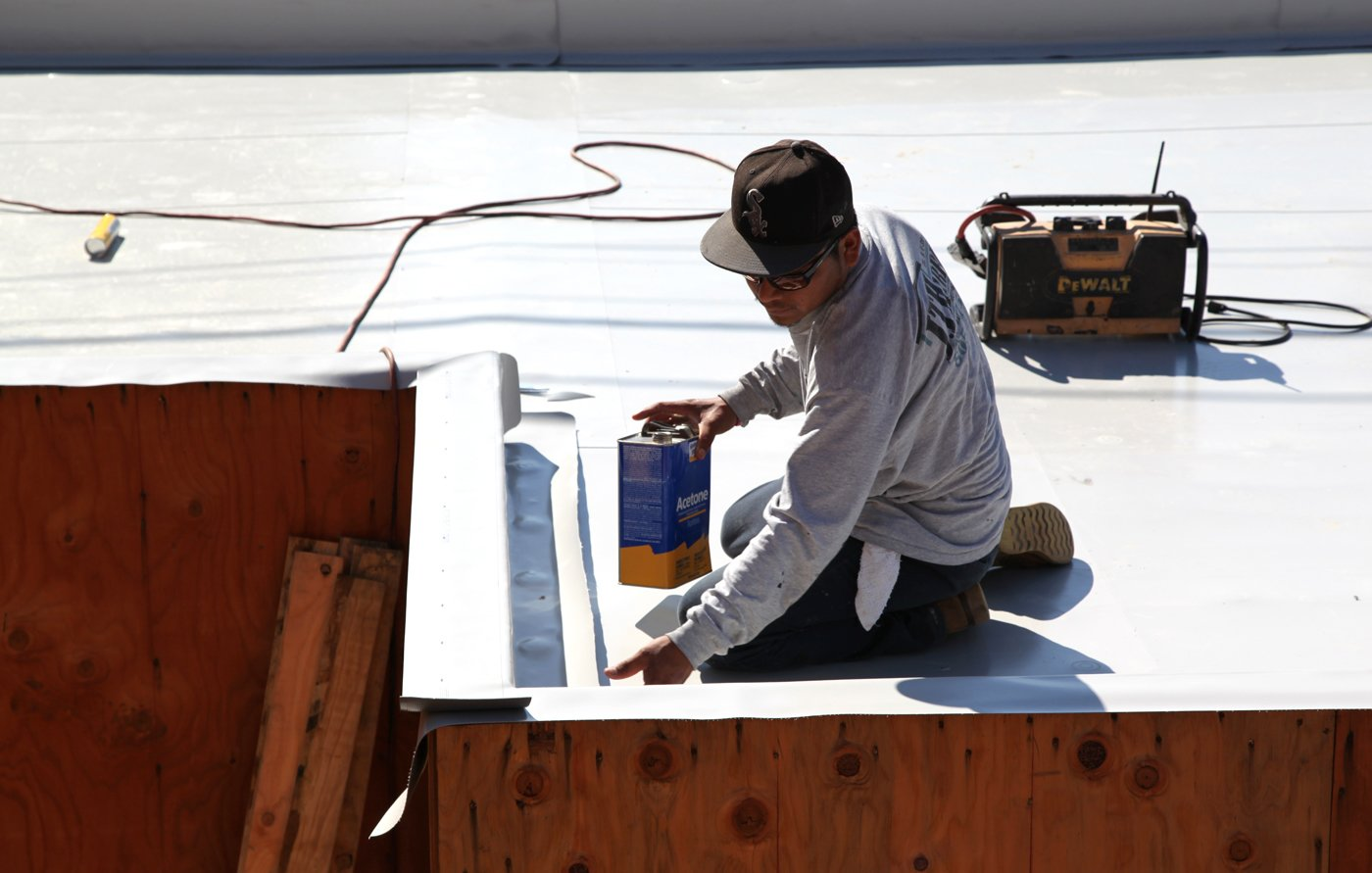 A roof installer from J.T. Harris finishes installing the Versico PVC membrane on a garage roof parapet. The parapet will have a black metal coping installed as the final finish.  Photo 8 of 9 in Dwell Home Venice: Part 14