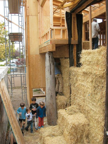 """Straw Dogs  """"Straw is basically a waste material,"""" says Tilt. """"Farmers used to burn rice straw, but now they're baling it up to sell, which takes tons of CO2 out of the atmosphere."""" It's also a stellar source of insulation, both thermal and acoustic. With the guidance of structural engineer Kevin Donahue, Arkin Tilt, the couple, and a group of their friends and neighbors pitched in for a daylong """"bale raising."""" To minimize the straw's volume within the walls (they used 150 bales), the architects tipped the bales on edge, placed them between structural wood I-joists used as posts, and finished them off with welded wire mesh and lime plaster."""