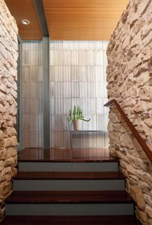 A striated concrete wall designed by Pollen Architecture & Design contrasts with the rough limestone rock of the home's existing stair column.
