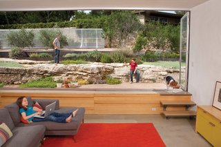 The family room is situated at the apex of the house, with picturesque views that extend   up the meticulously landscaped north slope. The concrete floor sits just low enough that the main elements of the scene—the succulent garden and large limestone ledges—are at eye level. A bank of NanaWall folding windows breaks up the fourth wall.