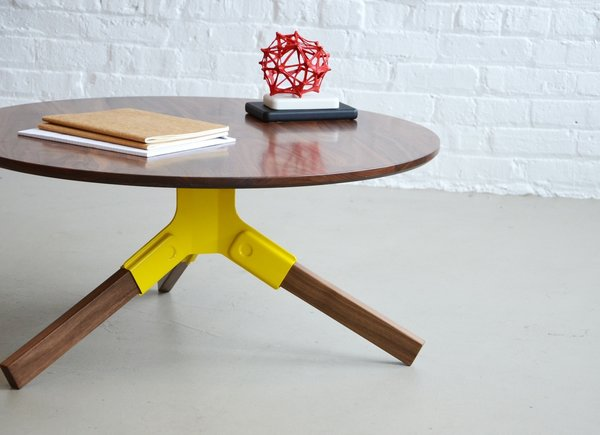 The walnut Conrad coffee table's legs snap into a stamped steel bracket, which comes in powder-coated black, ivory, or this sunny shade of yellow ($1,150).