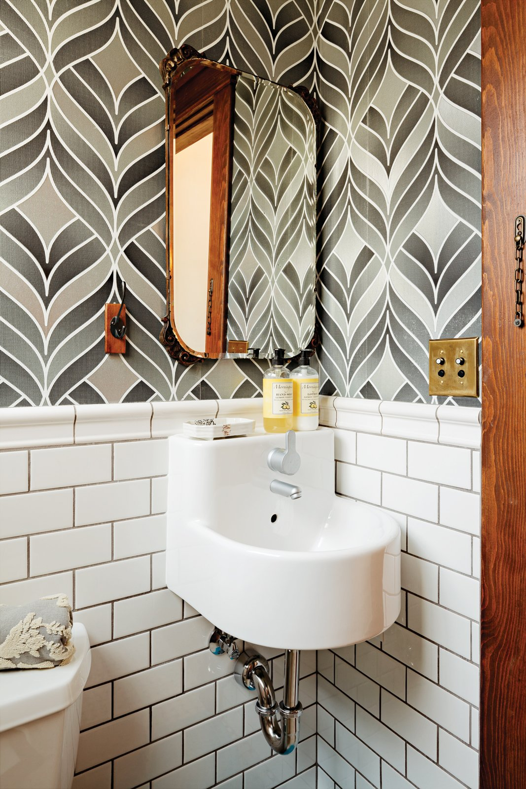 Bath Room, Wall Mount Sink, and Subway Tile Wall Playful wallpaper from Graham & Brown livens up the house's otherwise staid   powder room, which also contains a   pint-size Ikea sink.  Inspiring Wallpapers for the Modern Home by Kelsey Keith from Wallpaper That Fixes Walls