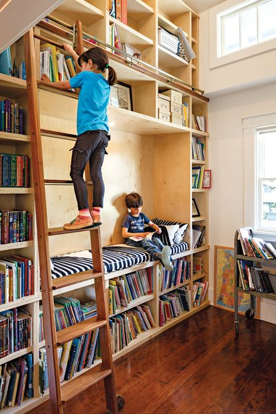 "A former   closet was transformed into a double-height library, complete with a reading nook and a rolling ladder from Spiral   Stairs of America. ""That's my   favorite part of the house,"" says Dan.   ""When I see Stella reaching for a book,   there's nothing better."""