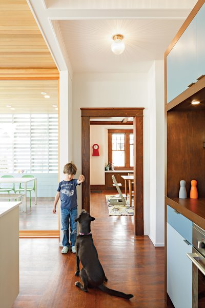 To help define the kitchen, the architects designed a wall of storage with cubbies   on one side and a pantry with appliances on the other. Colorful doors add   a playful touch, and DP3 Series cabinet pulls from Doug Mockett & Company keep the surfaces streamlined.