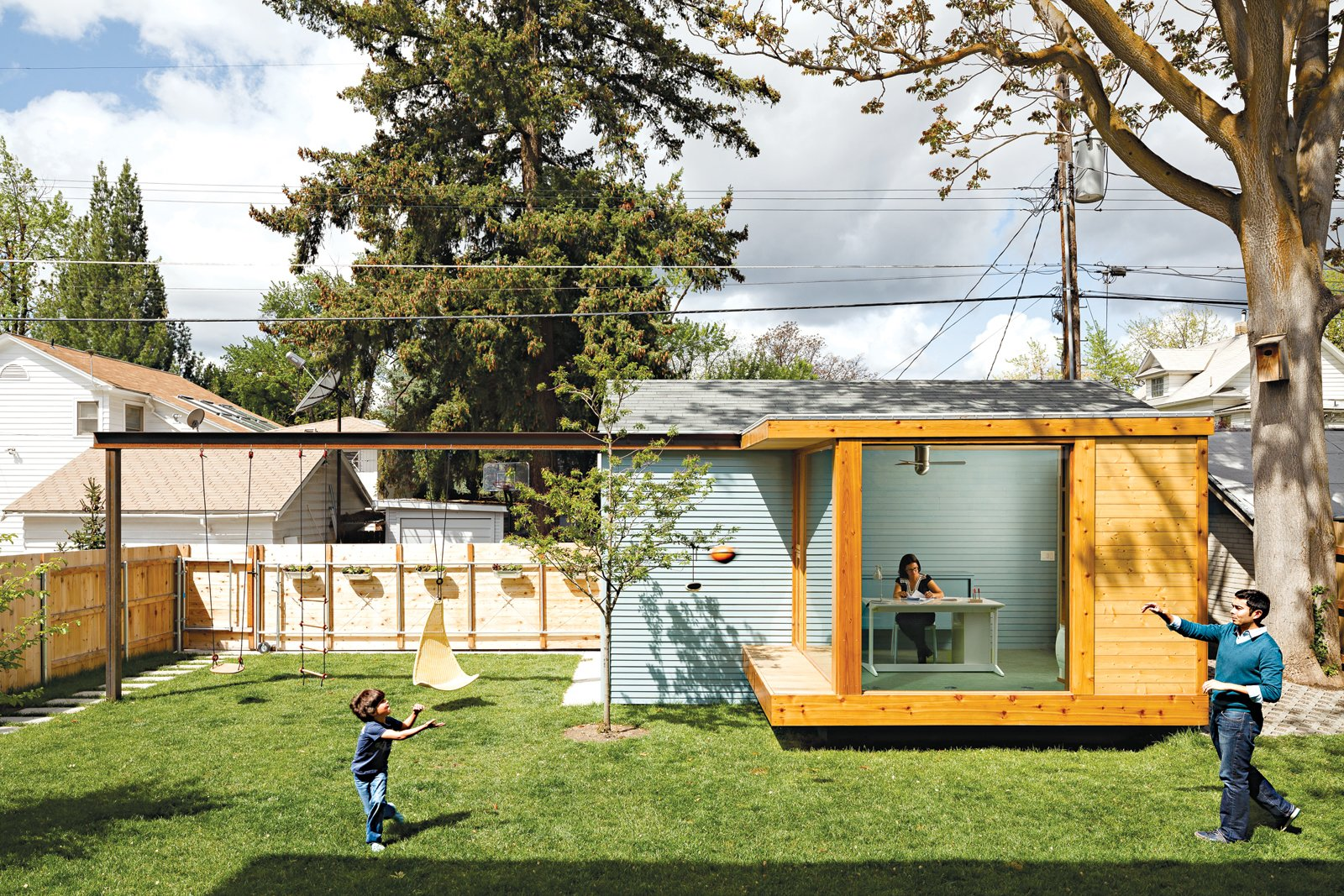 "Shed & Studio, Living Room Room Type, Family Room Room Type, and Den Room Type Work It  ""We wanted to open up the back of the house, but there's nothing to look at,"" says Dana. ""So we decided to put something in our yard as a focal point, to create our own view."" The architects came up with a glass-walled studio, which Dana uses as   her home office. The architects mounted a steel I-beam that spans the yard, with holes drilled at eight-inch intervals for maximum flexibility of use. Right now it's used for Ikea play equipment, but later they plan to hang a hammock and a movie screen.  ikea.com  Best Photos from An Airy Addition to a Historic Boise Home"