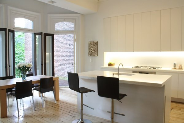 The kitchen is decidedly more modern, with large glass doors opening onto the patio.