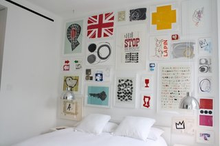 The master bedroom is mostly white, which makes this fantastic wall of art really pop.