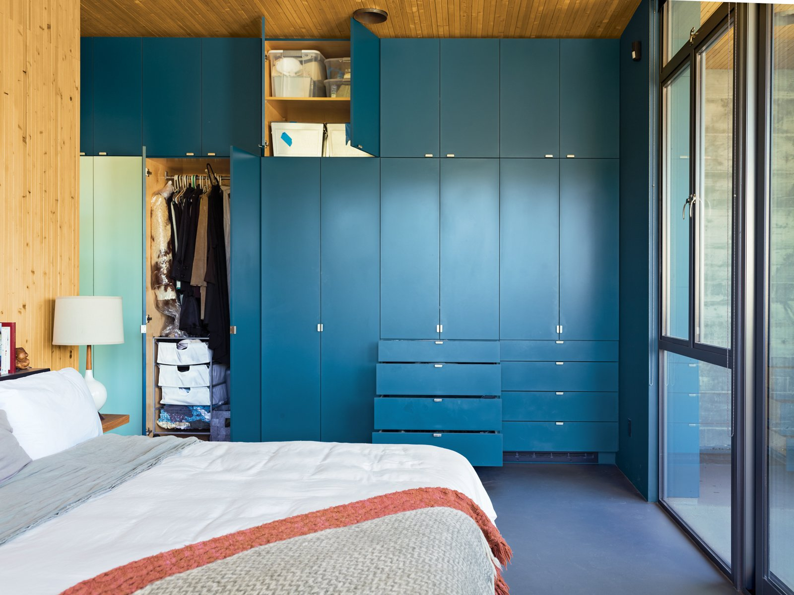 "Bedroom and Storage In such a small space ""you have to organize, and every piece takes a decision,"" says resident Heidi Wright. The couple keep things they use less frequently, like guest bedding, in the higher cabinets.  Photos from Malibu Canyon House with a View"