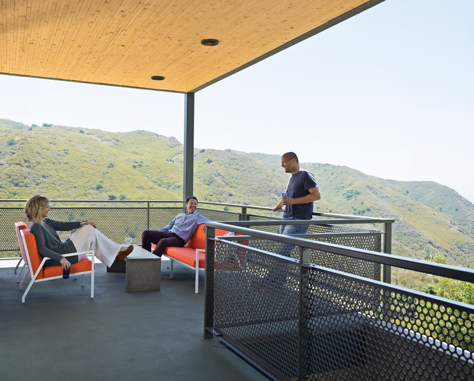 "Outdoor, Large Patio, Porch, Deck, and Concrete Patio, Porch, Deck Wright and Keffer (standing) hang out on their deck with Bolander, who lives just across the road. The chairs, designed by Bolander, are upholstered in Sunbrella fabric.  Search ""staircasetread--metal"" from Malibu Canyon House with a View"