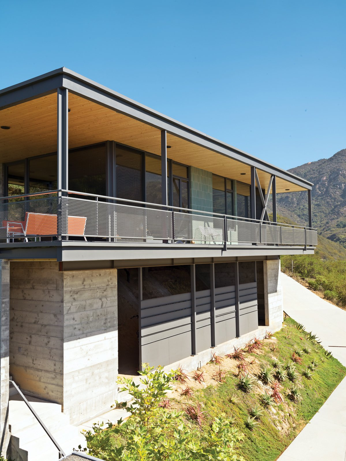 Exterior, Flat RoofLine, Concrete Siding Material, and House Building Type Fir slats on the wall and ceiling run through to the outdoors, visually expanding the space.  Photo 8 of 9 in Malibu Canyon House with a View