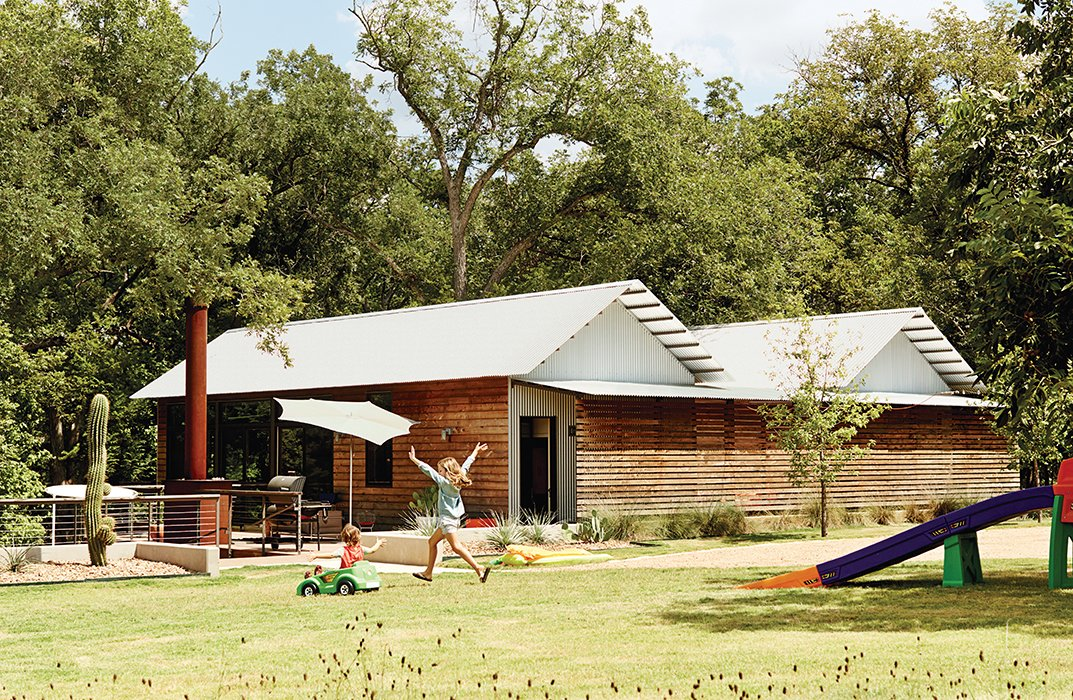 Exterior, Prefab Building Type, Wood Siding Material, and House Building Type Scott Wallace and Tara Coco turned to Lake|Flato Architects and its modular Porch House system for a family compound on the banks of the Blanco River in Wimberley, Texas. The design integrates private spaces with public gathering spots, including a deck that serves as an outdoor living room.  Superb Single-Story Homes by Luke Hopping from Modular Compound is the Ultimate Retreat for Three Generations