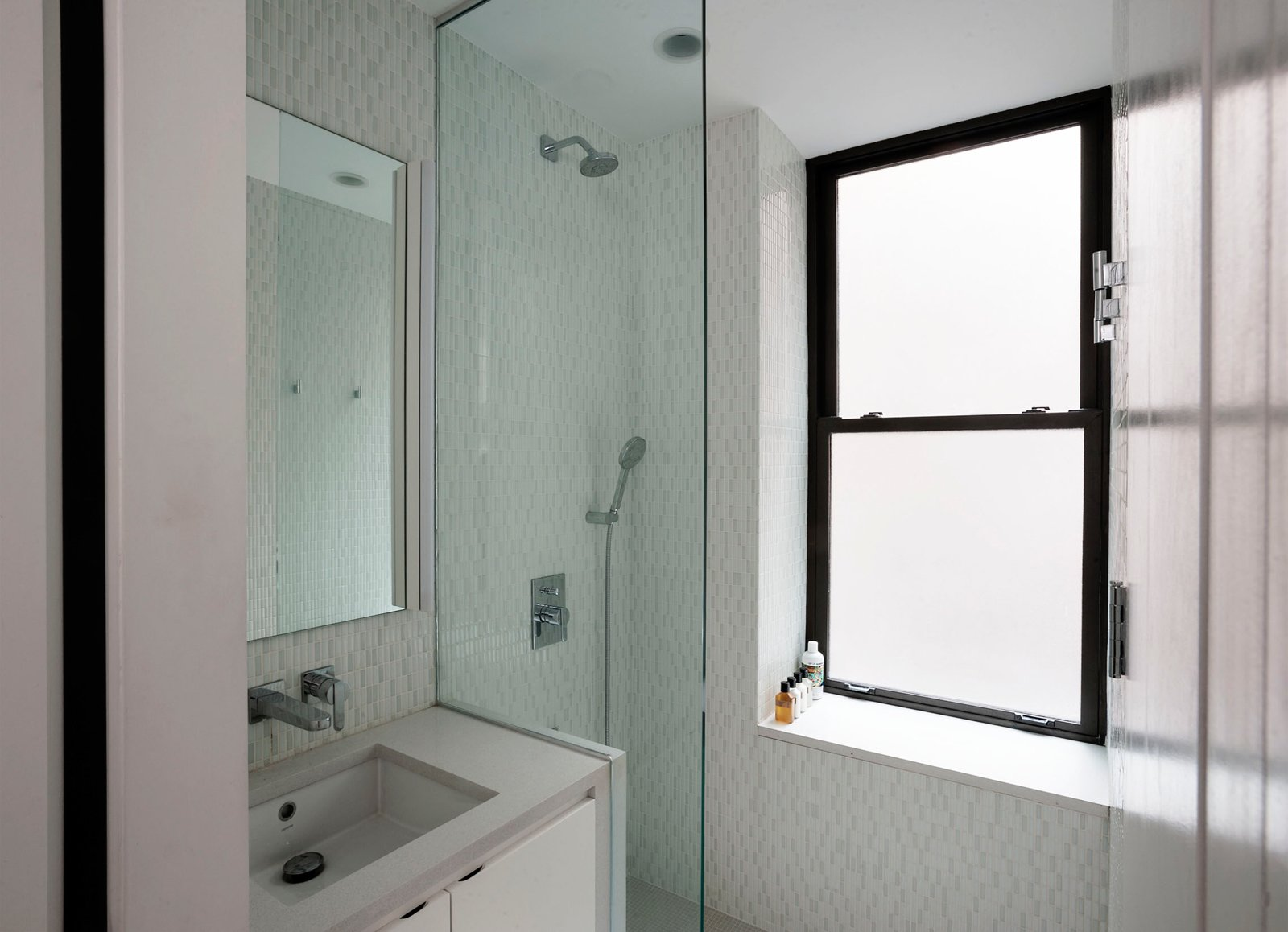 In the shower a pre-existing window sill was used to create a comfortable shower seat, while the glass enclosure keeps the bathroom feeling open.  Photo 10 of 12 in Small Space Living by LifeEdited