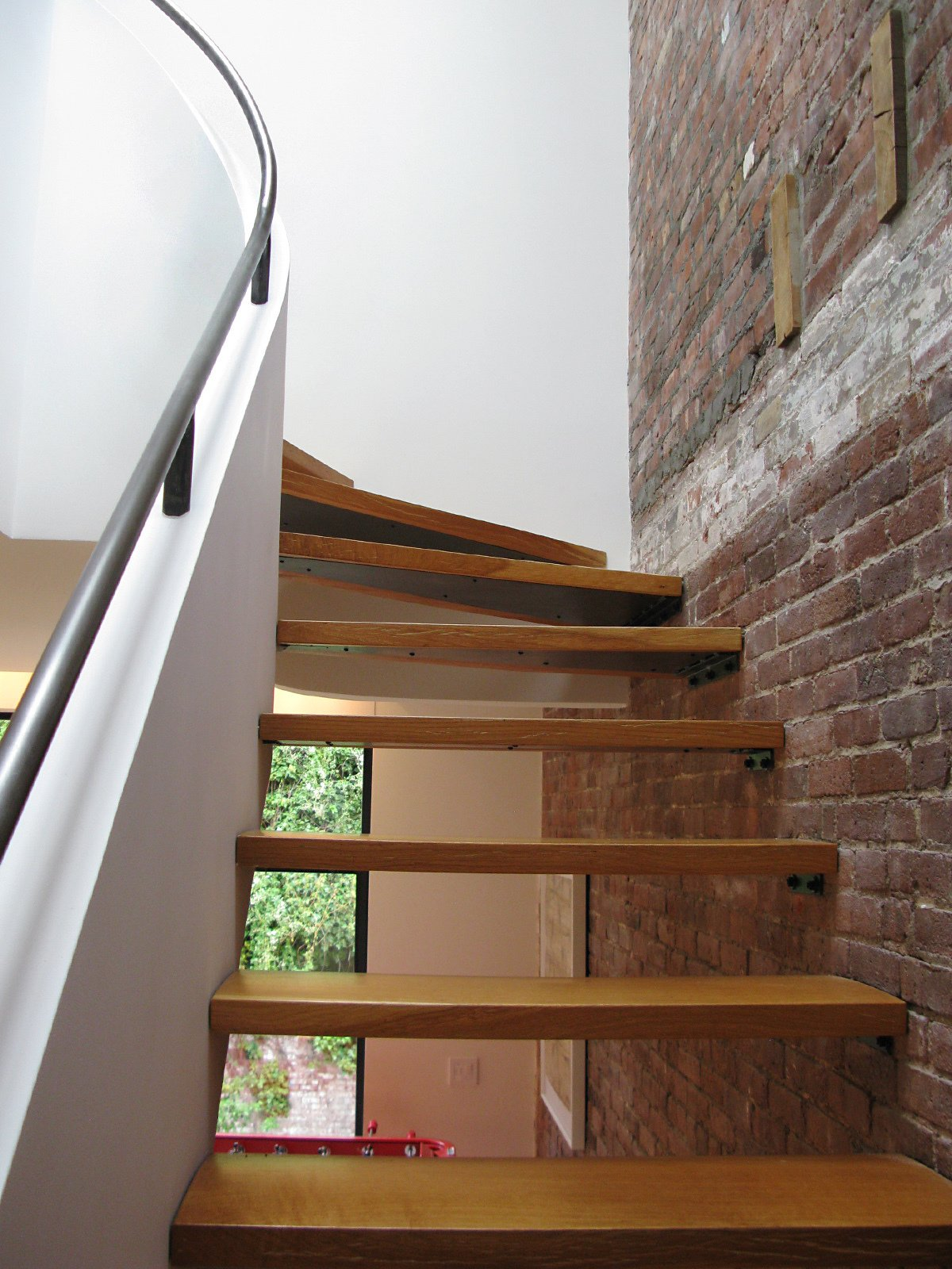 Thick planks lead visitors up the staircase and compliment the wooden-beam details left exposed from the previous layout.  Photo 3 of 51 in City Modern Home Tours: Brooklyn