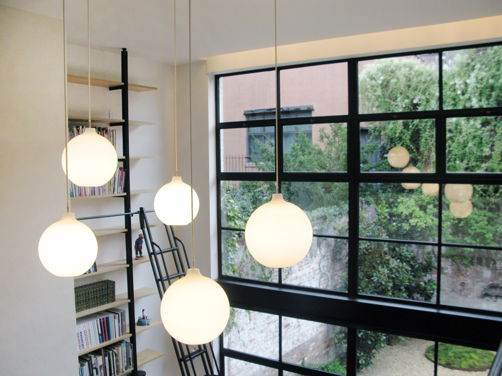 A view of the vertical library and garden beyond the 16-foot-tall wall of windows.  Photo 5 of 51 in City Modern Home Tours: Brooklyn