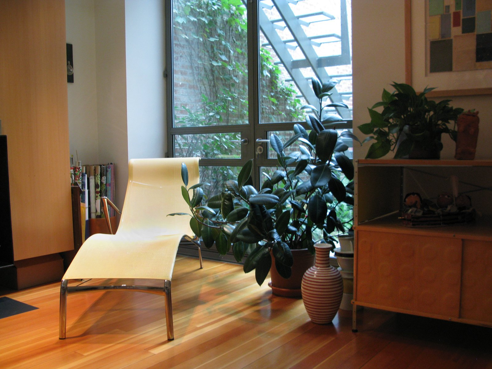 """Aside from the cohesion of past detailing and present decoration, the townhouse also blends inside and outside elements. Windows show glimpses of the garden outside, and potted plants are as well-placed at the artworks.  """"Plants make it feel more human and alive,"""" the owner says.  Photo 15 of 51 in City Modern Home Tours: Brooklyn"""