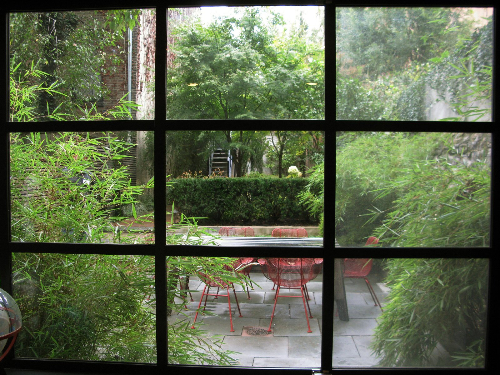 Here's a view of the garden through custom steel windows fabricated for the house by the owners' artist friend.  Photo 28 of 51 in City Modern Home Tours: Brooklyn