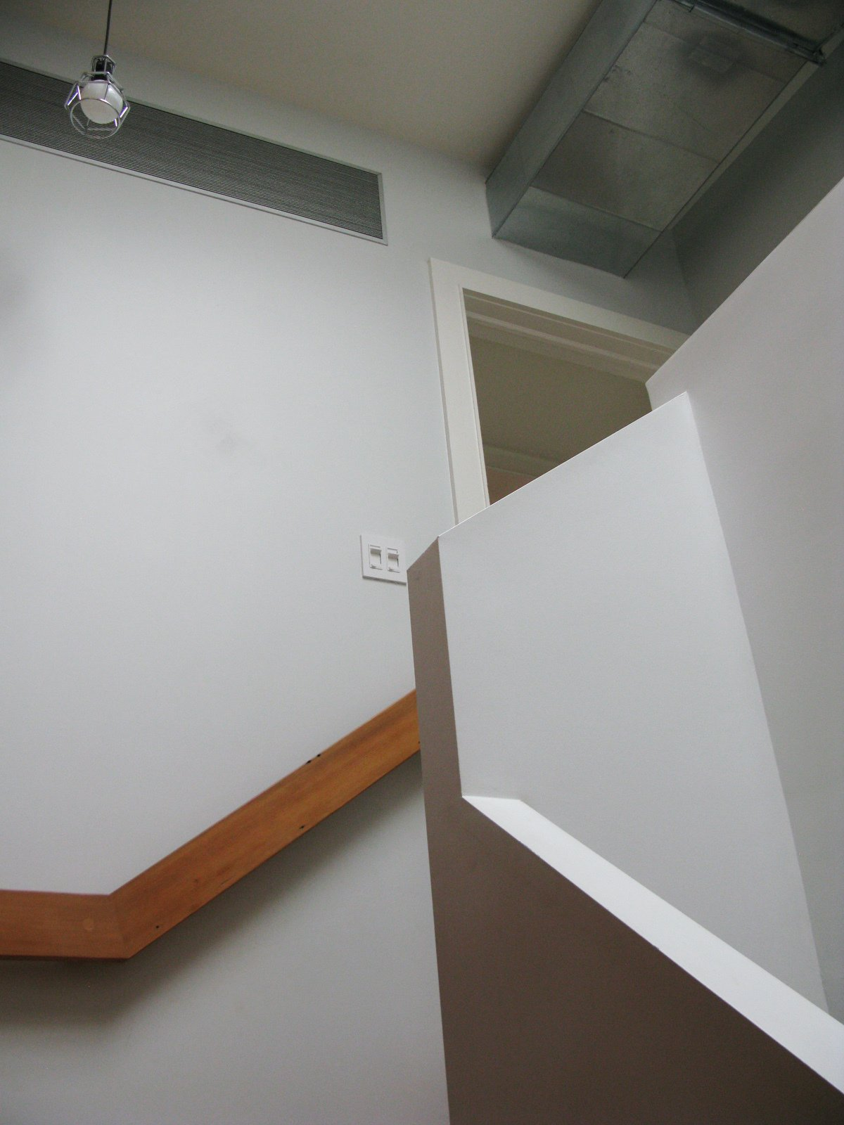 """Lines of the staircase and railing play with one another in a visually pleasing way, and the exposed air ducts work with the comfortable, no nonsense design. """"You don't notice the ducts by being frank about them,"""" Bischoff says of the visible conduit.  Photo 48 of 51 in City Modern Home Tours: Brooklyn"""