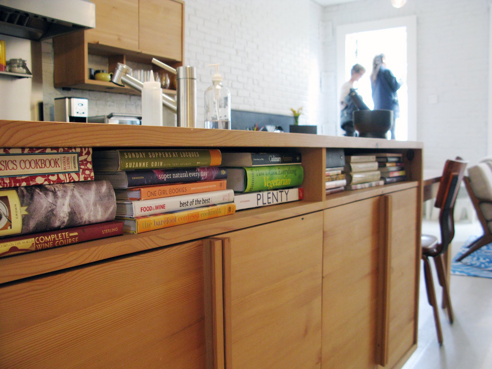 """Cubby holes under the kitchen counter house cookbooks. The cabinets are made from salvaged wood. """"The kitchen is where they like to be at home,"""" Bischoff says. """"That's why it's in the middle of the floor plan.""""  Photo 51 of 51 in City Modern Home Tours: Brooklyn"""