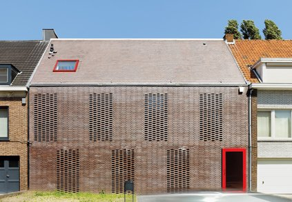"""In this Facade Focus on brick, Tom Verschueren, of Mechelen, Belgium-based DMVA Architects, created a closed street-side facade with an open backside facing the garden, totally glazed from the ground up to the saddleback roof. On the street side, the only true opening is the door; the seven tall, slim windows are screened by what Verschueren calls """"knitted"""" bricks. """"In this part of Belgium, 90 percent of the houses are built with brick,"""" says Verschueren. """"It's a classic material that we tried to use in House BVA in a totally different way.""""  Brick Houses from Around the World  by Matthew Keeshin from Modern Home Facades"""