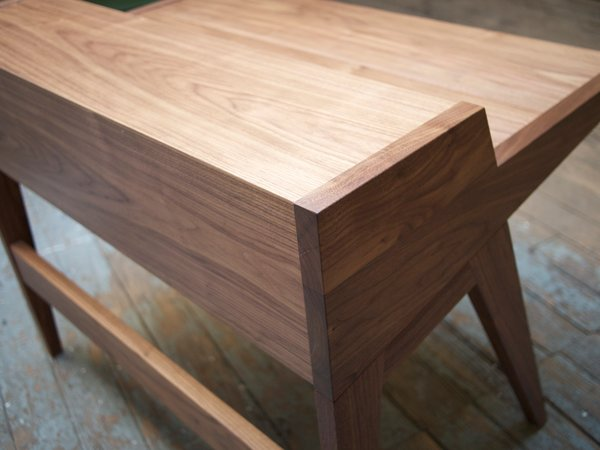 """The desk's sides, legs, stretcher, and drawers are made from solid wood. With the design of the desk, the top could not be made of solid wood otherwise there would be problems with wood movement over time. Each Laura Desk has a top made of plywood with 1/16""-thick, hand-cut solid veneer on its writing surface. Standard veneer, even on premium plywood is less than 1/32"" thick, and this wouldn't last over time. With the thicker veneer, we're creating an heirloom desk that will last for generations."""