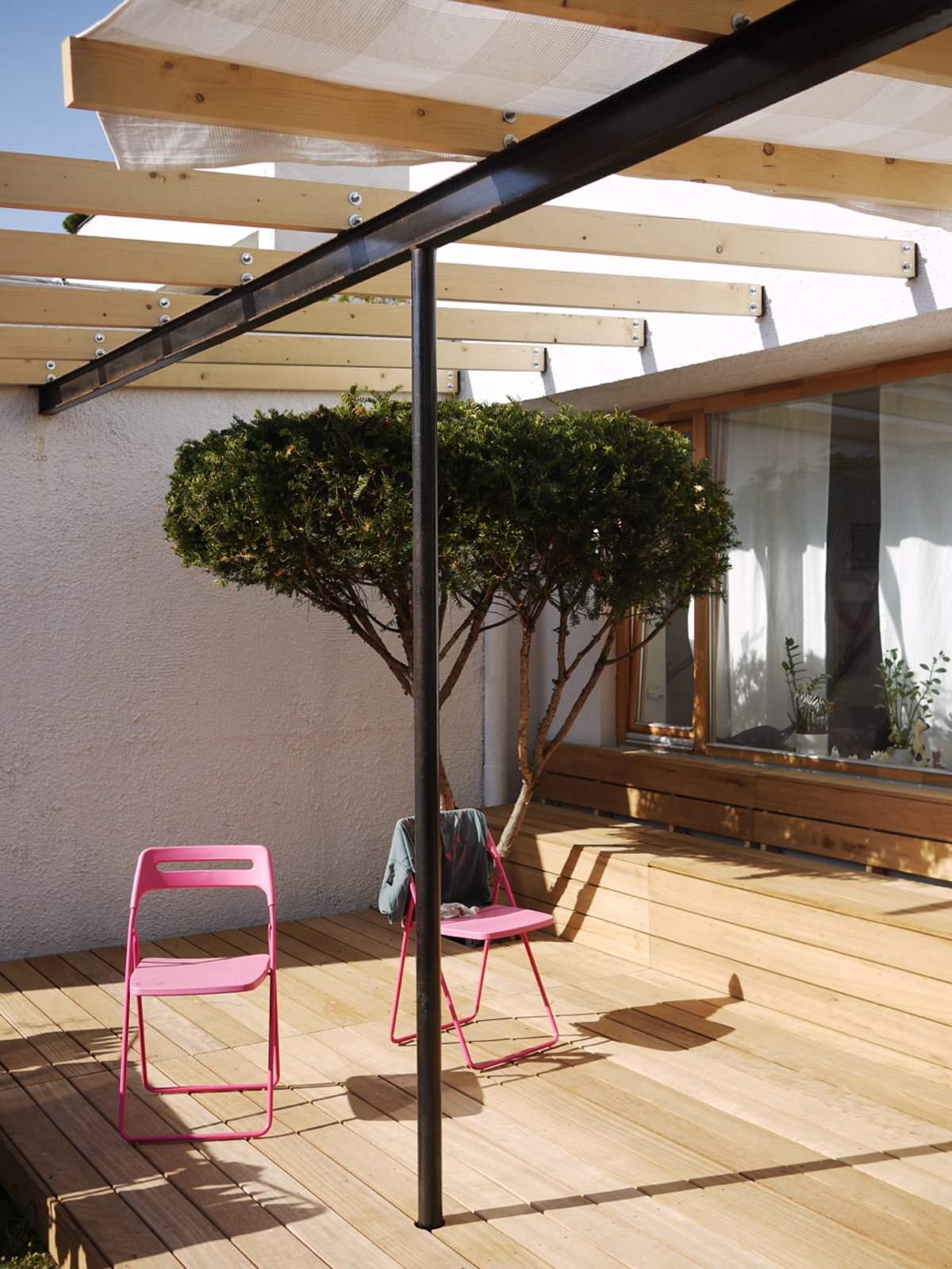 Being on the ground floor has its benefits—namely a bit of outdoor space. The black I-beam supporting the canopy of exposed joists offers a nice contrast to the wood above and below. Pink chairs do the trick as well.  NHR Apartment by Gut Gut by Aaron Britt